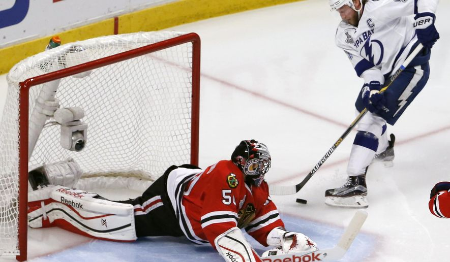 Chicago Blackhawks goalie Corey Crawford, left, makes a save on a shot by Tampa Bay Lightning's Steven Stamkos during the second period in Game 6 of the NHL hockey Stanley Cup Final series on Monday, June 15, 2015, in Chicago. (AP Photo/Charles Rex Arbogast)