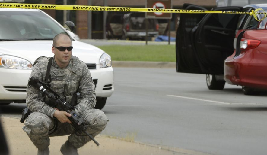 A member of an Air Force security detail guards the front gate of little Rock Air Force Base near Jacksonville, Ark., Monday, June 15, 2015.  Military officials said two people were hospitalized after shots were fired when a civilian attempted to enter Little Rock Air Force Base. The Jacksonville police department said the would-be intruder was injured and taken into custody. (AP Photo/Danny Johnston)