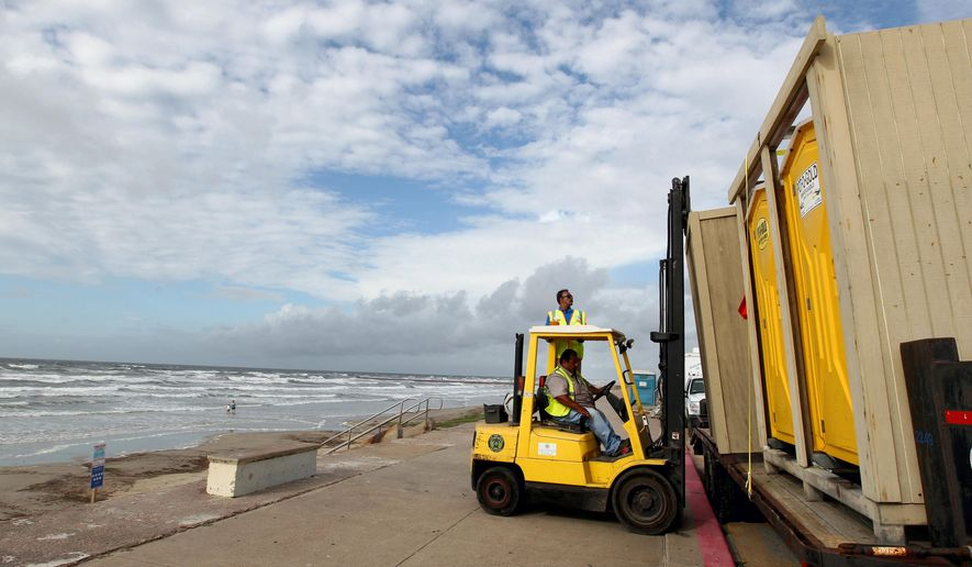 Jesse Ojeda, beach cleaning operations manager for the Galveston Island Park Board of Trustees, helps Rey Soto load portable toilets onto a trailer, Monday, June 15, 2015, as they prepare the seawall for the tropical disturbance headed toward the Gulf coast. A low pressure area located over the south central Gulf of Mexico is being monitored by the National Hurricane Center for possible tropical cyclone formation as it moves northwest towards the middle and upper Texas coast. (Jennifer Reynolds/The Galveston County Daily News via AP)