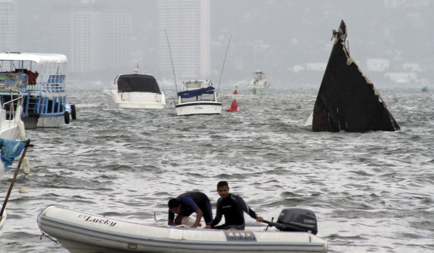 Two men navigate near a nearly sunken boat after the passing of hurricane Carlos in the Pacific resort city of Acapulco, Mexico, Sunday, June 14, 2015. Tropical Storm Carlos churned up strong winds and waves Sunday while threatening to regain strength as it trudged up Mexico's Pacific coast. (AP Photo/Bernandino Hernandez)