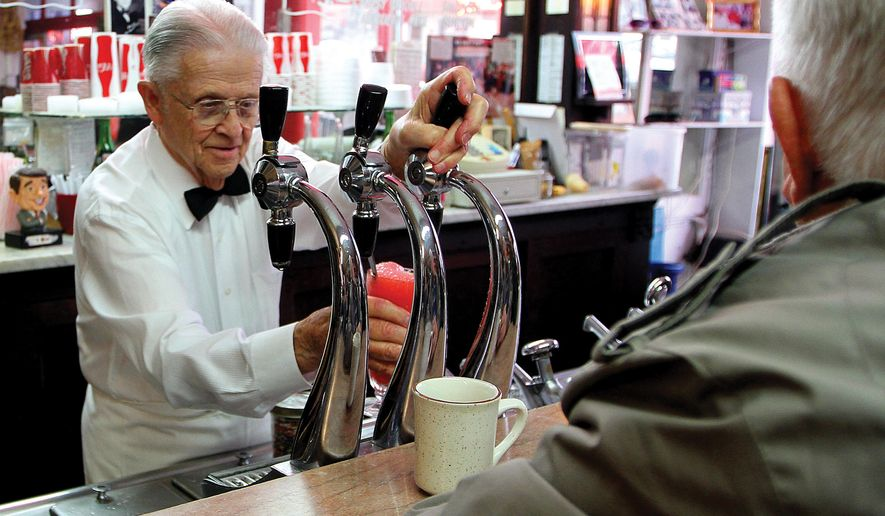 This Dec. 28, 2012 photo shows George Nopoulos using the soda fountain from behind the counter at the Wilton Candy Kitchen in Wilton, Iowa. He made his first cherry Coke with the soda fountain when he was eight-years-old. Nopoulos, the longtime owner of a landmark Iowa soda fountain, has died Sunday, June 14, 2015, of natural causes in Wilton at age 95. (John Schultz/The Quad City Times via AP)