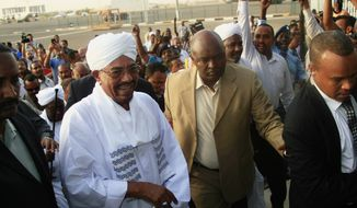 Hundreds of supporters welcome Sudanese President Omar al-Bashir, center left, on his arrival from South Africa as he walks through the crowd at the airport in Khartoum, Sudan, Monday, June 15, 2015. Al-Bashir arrived in Khartoum to cheers of supporters after leaving South Africa, where a court had ordered his arrest based on an international warrant for war crimes charges. (AP Photo/Abd Raouf)