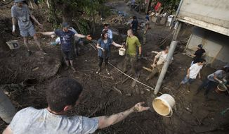 A volunteer throws a bucket to another volunteer as they clear the mud at a house after Sunday's flooding, in Tbilisi, Georgia, Monday, June 15, 2015. (AP Photo/Pavel Golovkin)