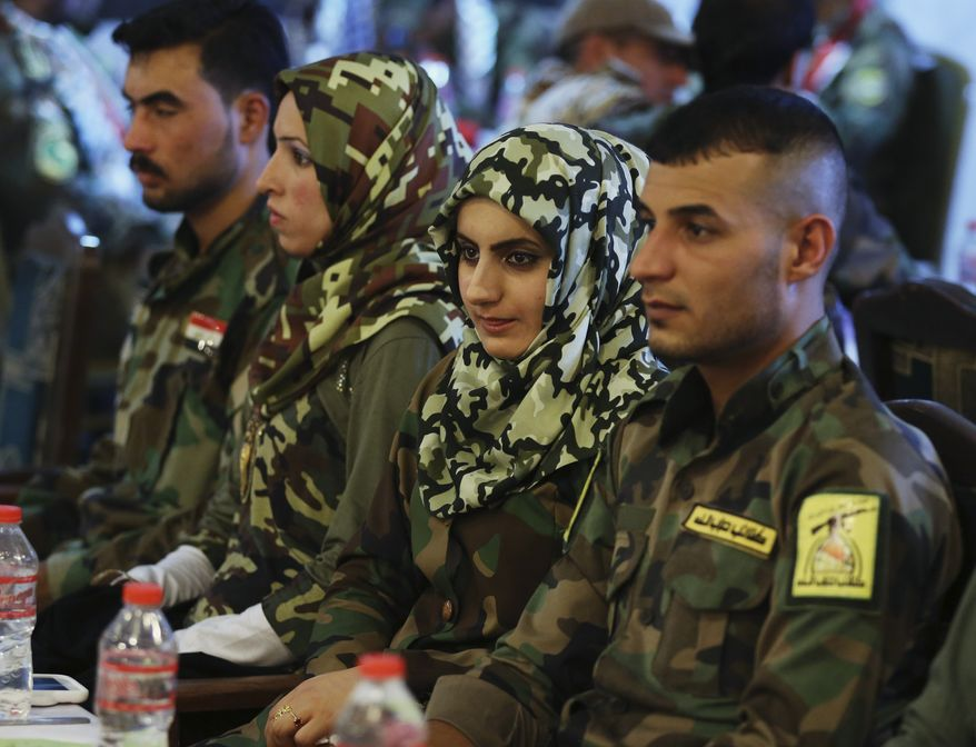 Grooms from Iraq's Shiite militia and their brides attend a mass wedding ceremony at a club in Karrada neighborhood of Baghdad, Iraq, Monday, June 15, 2015. About 125 couples got married at the ceremony Monday sponsored by the government. (AP Photo/Hadi Mizban)