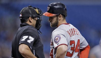 Washington Nationals' Bryce Harper (34) talks to home plate umpire Jim Reynolds after being called out on strikes during the first inning of a baseball game against the Tampa Bay Rays Monday, June 15, 2015, in St. Petersburg, Fla. (AP Photo/Chris O'Meara)