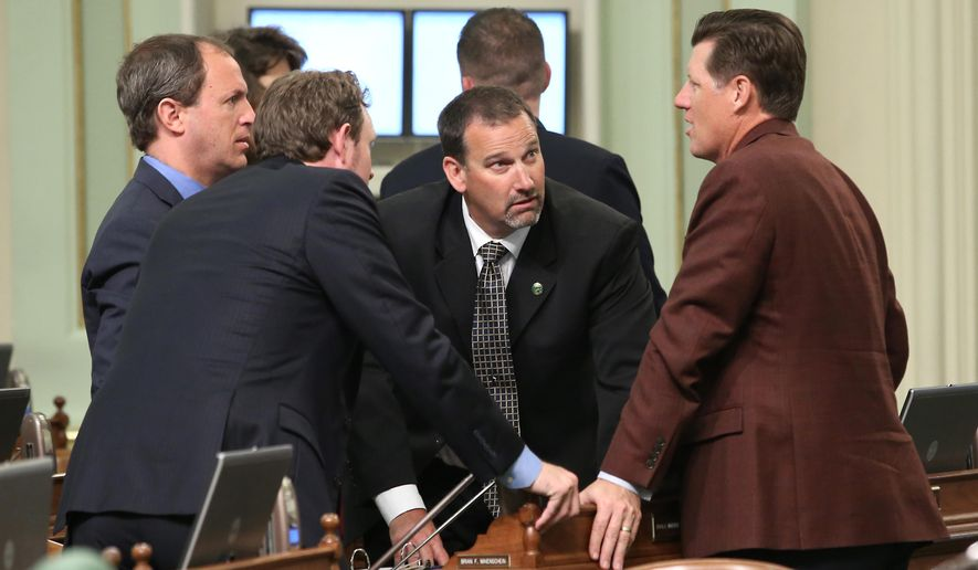 Republican Assembly members, from left, Brian Maienshcein, of San Diego, James Gallagher, of East Nicolaus, Brian Dahle of Bieber and Brian Jones, of Santee, right, huddle before the Assembly takes up the state budget at the Capitol in Sacramento, Calif., Monday, June 15, 2015. Legislative Democrats have not reached a deal with the governor on spending levels, but are expected to approve their own plan and continue negotiations with Gov. Jerry Brown ahead of the July 1 start of the fiscal year. (AP Photo/Rich Pedroncelli)
