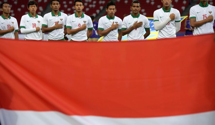 The Indonesian soccer team sings their national anthem ahead of their game against Vietnam for the bronze medal at the SEA Games in Singapore, Monday, June 15, 2015. After a surge of optimism as Indonesia qualified for the Southeast Asian Games semifinals, the country's ban from international football will go into full effect following deflating, back-to-back 5-0 losses. (AP Photo/Joseph Nair)