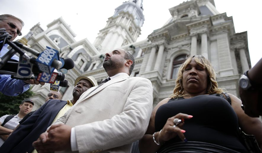 Tanya Brown-Dickerson, right, the mother of Brandon Tate-Brown, who was shot by Philadelphia police as he ran during a traffic stop, listens to attorney Brian Mildenberg, center, during a news conference Monday, June 15, 2015, outside of City Hall in Philadelphia. Brown-Dickerson is suing the city over the fatal shooting of her son last December (AP Photo/Matt Rourke)