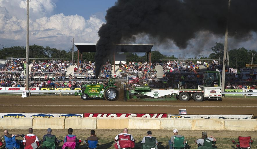 """In this Saturday, June 13, 2015 photo, spectators watch as the pro stock tractor """"KING OF DEERES"""" is driven by Cory Hoffman, of Richmond, Ohio during the Spring Nationals Truck & Tractor Pull competition of the Lucas Oil Champions Tour, at the Clinton County Fairgrounds in Wilmington, Ohio. The black smoke is from the tractor's diesel engine. (AP Photo/John Minchillo)"""