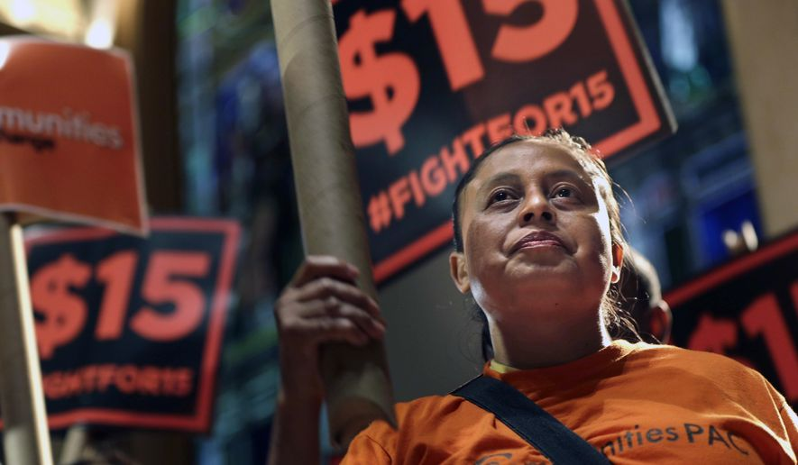 Demonstrators rally for a $15 minimum wage before a meeting of the wage board in New York, Monday, June 15, 2015. The board, created by Gov. Andrew Cuomo, will consider a minimum wage increase for New York's fast-food workers. (AP Photo/Seth Wenig)