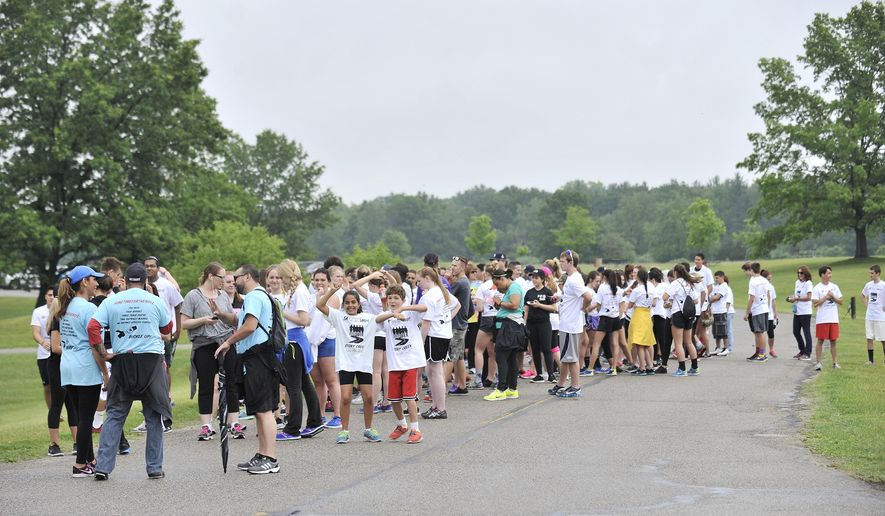 Participants line up for the start of the 5-K walk at Stony Creek Metropark in Shelby Township, Mich. on Sunday, June 14, 2015. More than 200 people took part in a fundraiser in honor of five suburban Detroit teenagers involved in a car crash that killed three of them. (Robin Buckson/The Detroit News via AP)
