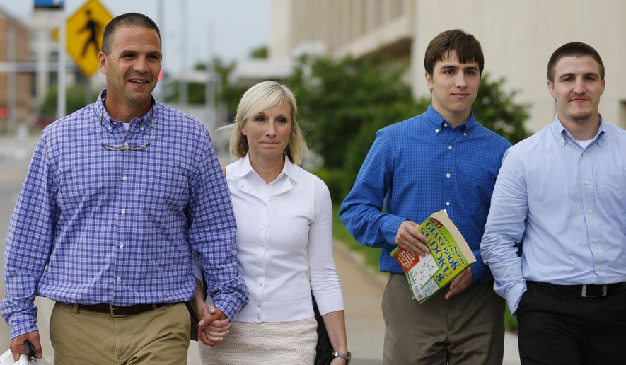 Kyle Durham, left, and Melissa Durham, second from left, hold hands as they leave the Federal Courthouse in Oklahoma City, following another day of testimony in the federal trial of their son, Matthew Lane Durham, Monday, June 15, 2015. At right are their other two sons, Josh Durham, right, and Zac Durham. Matthew Lane Durham is accused of 17 counts of sexual misconduct with children in Nairobi, Kenya.   (AP Photo/Sue Ogrocki)
