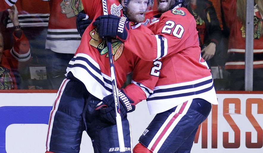 Chicago Blackhawks' Duncan Keith, left, is congratulated by teammate Brandon Saad after scoring a goal during the second period in Game 6 of the NHL hockey Stanley Cup Final series on against the Tampa Bay Lightning Monday, June 15, 2015, in Chicago. (AP Photo/Nam Y. Huh)