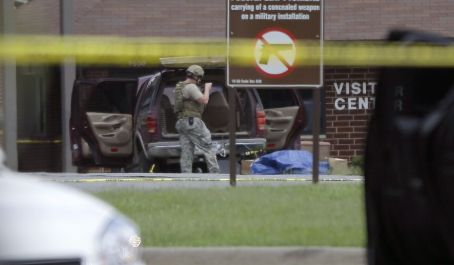 A man dressed in military attire examines contents of a SUV at the front gate of little Rock Air Force Base near Jacksonville, Ark., Monday, June 15, 2015.  Military officials said two people were hospitalized after shots were fired when a civilian attempted to enter Little Rock Air Force Base. The Jacksonville police department said the would-be intruder was injured and taken into custody. (AP Photo/Danny Johnston)