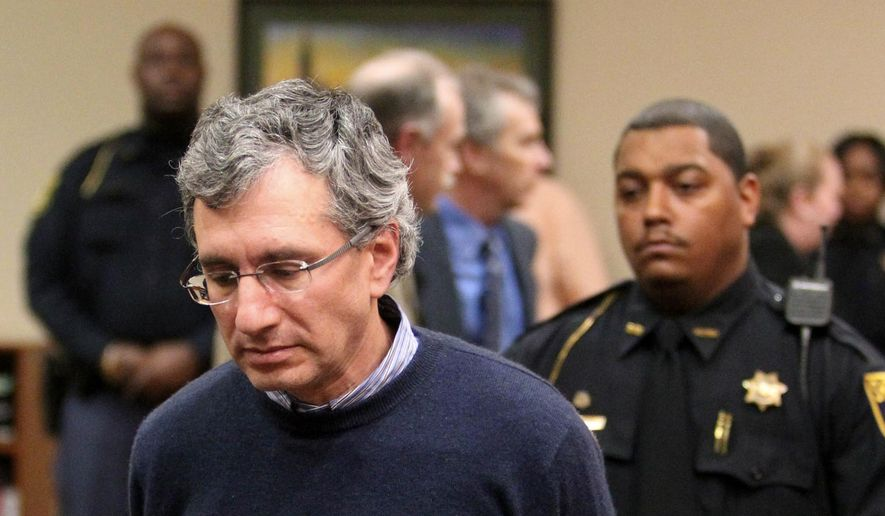 Hemy Neuman is escorted by DeKalb County Deputies after his sentencing during the his trial in the DeKalb County Courthouse, in Decatur, Ga., in this March 15, 2012, file photo. The Georgia Supreme Court has reversed the conviction of Neuman, who was involved in a love triangle that led to a killing outside an Atlanta-area preschool. The court announced the 6-1 decision involving Neuman in an opinion released Monday morning, June 15, 2015. (Jason Getz/Atlanta Journal-Constitution via AP, File)