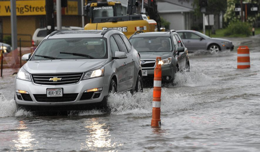 Motorists try to drive through rising water levels Monday, June 15, 2015, in Appleton, Wis. Appleton's Department of Public Works and local law enforcement agencies have been overwhelmed with callers reporting flooded streets. (Dan Powers/The Post-Crescent via AP) NO SALES