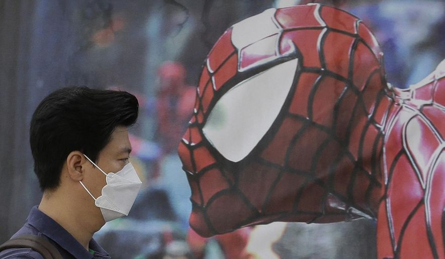 FILE - In this Wednesday, June 10, 2015 file photo, a South Korean man wearing a mask as a precaution against the Middle East Respiratory Syndrome virus walks by a Spider-Man poster advertising a musical for children in Seoul, South Korea. MERS has infected nearly 100 and caused nine deaths in South Korea, but experts say the virus mainly spreads through close contact with an infected person. (AP Photo/Ahn Young-joon, File)