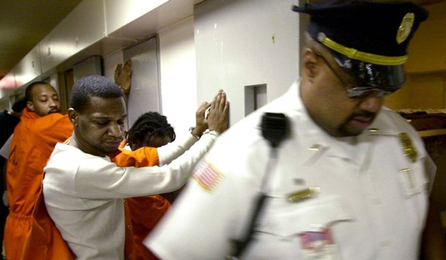 Inmates Donnell Howard (foreground) and John Lawrence (background) wait handcuffed outside their cells while corrections officers search for contraband and weapons during a suprise search at the Washington DC Central Detention facility in Washington DC on Thursday, May 30, 2002. The unannounced searches take place at least once a year and are planned so as to not allow inmates time to dispose of the weapons. Inmates are required to have paperwork for items such as authorized medication. ( Gerald Herbert / The Washington Times )