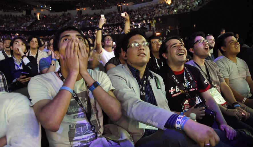 Attendees react to a video game demonstration during the Sony Playstation at E3 2015 news conference at the Los Angeles Sports Arena on Monday, June 15, 2015, in Los Angeles. (Photo by Chris Pizzello/Invision/AP)