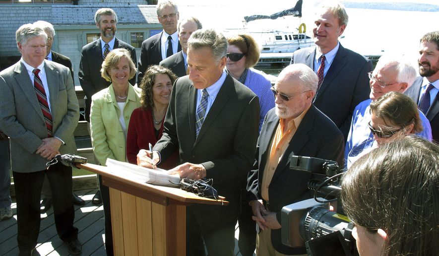 Vermont Gov. Peter Shumlin, center, signs into law the Vermont Clean Water Act, Tuesday June 16, 2015 on the Lake Champlain waterfront in Burlington, Vt. The new law is designed to clean up the lake by reducing pollutants that run into it. Shumlin said the law is an effort to correct a problem that has been centuries in the making. (AP Photo/Wilson Ring)