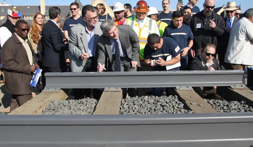 FILE - In this Tuesday, Jan. 6, 2015 file photo, dignitaries and VIP's line up to sign a portion of the rail at the California High Speed Rail Authority ground breaking event, Tuesday, in Fresno, Calif. A transportation bill passed as part of the Democratic state budget would reduce the reporting requirements for the California High-Speed Rail Authority, which critics say is a move to lessen transparency on the controversial $68 billion project. The agency that oversees the project says it brings reporting in line with its annual budgeting and reporting cycles. (AP Photo/Gary Kazanjian, File)