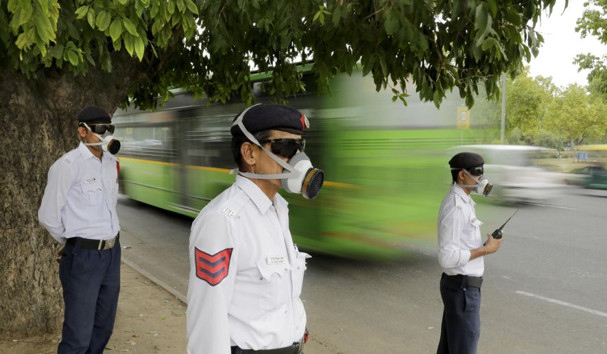 In this Tuesday, June 9, 2015 photo, Indian policemen wear masks as they control traffic in New Delhi, India. Never mind lowering the rate of death from air pollution in India and China. Just keeping those rates steady will demand urgent action to clear the skies, according to a new report published Tuesday, June 16, 2015. (AP Photo/Altaf Qadri)