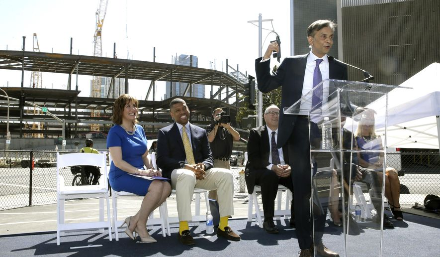 Vivek Ranadive, the majority owner of the Sacramento Kings, right, gestures to the new sports and entertainment center under construction that will be called the Golden 1 Center, during ceremonies in Sacramento, Calif., Tuesday, June 16, 2015. The team reached a 20-year-partnership with Golden 1 Credit Union, headquartered in Sacramento, a top credit union in California and the sixth-largest in the nation. Seated at left is Donna Bland, president and chief executive officer of Golden 1 Credit Union and Sacramento Mayor Kevin Johnson, second from left. (AP Photo/Rich Pedroncelli)