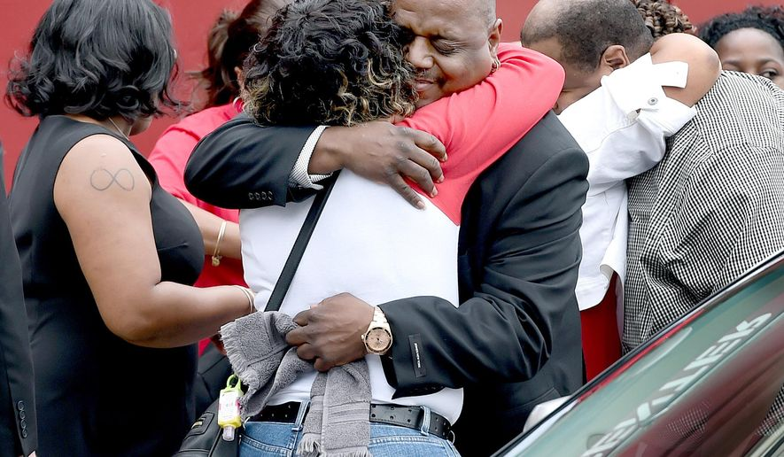 Michael Moore, center, father of deceased children Aleisha, 6, and Daaron, 7, is hugged outside of the Varick Memorial A.M.E. Zion Church before funeral services for the children in New Haven, Conn., Tuesday, June 16, 2015. The children's mother, LeRoya Moore, is detained on murder charges and wasn't allowed to attend the funeral. (Arnold Gold/New Haven Register via AP) MANDATORY CREDIT