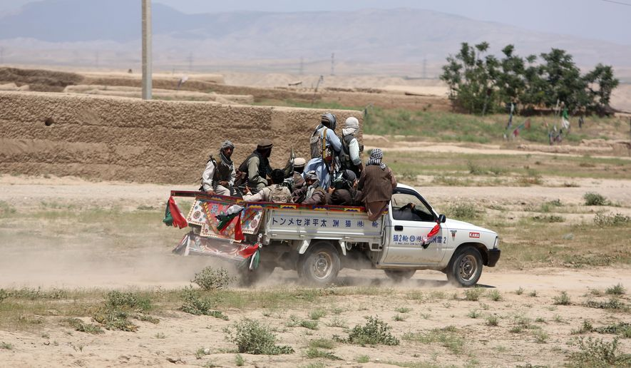 FILE - In this May 21, 2015 file photo, Afghan local militiamen ride a pick-up truck in Talawka village in Kunduz province, north of Kabul, Afghanistan. War-torn Afghanistan may soon have a defense minister, nine months after the new government was formed and amid some of the toughest fighting since the Talban's insurgency began 14 years ago. (AP Photo/Rahmat Gul, File)