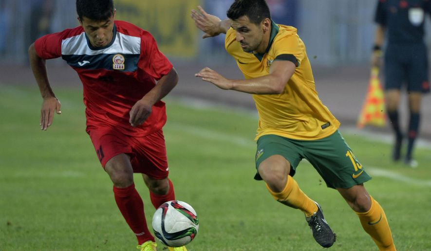 Kyrgyzstan's Farhat Musabekov, left, fights for the ball with Australia's Aziz Behich , during the 2018 World Cup qualifying  Round 2 Group B soccer match between Kyrgyzstan and Australia in  Bishkek, Kyrgyzstan, Tuesday, June 16, 2015. (AP Photo/Vladimir Voronin)