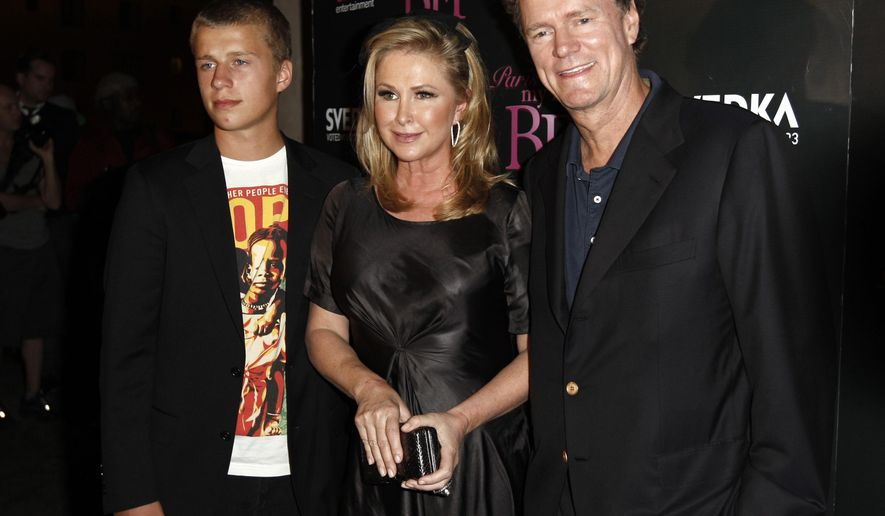 "FILE - In this Sept. 30, 2008 file photo, Conrad Hilton, left, Kathy Hilton, center, and Rick Hilton arrive at the launch party of new MTV series ""Paris Hilton's My New BFF"" in Los Angeles. Paris Hilton's youngest brother, Conrad, has been sentenced to community service and a $5,000 fine for disrupting a flight from London to Los Angeles in 2014. The 21-year-old was ordered Tuesday, June 16, 2015, to complete 750 hours of community service and undergo mental health and substance abuse treatment.   (AP Photo/Matt Sayles, File)"