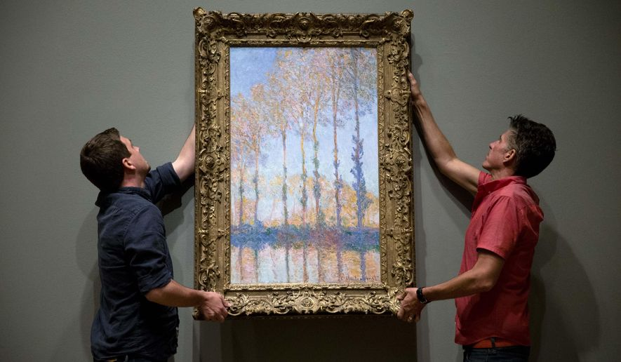 "Staff members Gus Boyce, left, and Eric Griffin place Claude Monet's oil on canvas ""Poplars on the Banks of the Epte River"" ahead of the exhibition ""Discovering the Impressionists: Paul Durand-Ruel and the New Painting,"" Tuesday, June 16, 2015, at the Philadelphia Museum of Art in Philadelphia. The showing is scheduled to run from June 24, to Sept. 13. (AP Photo/Matt Rourke)"