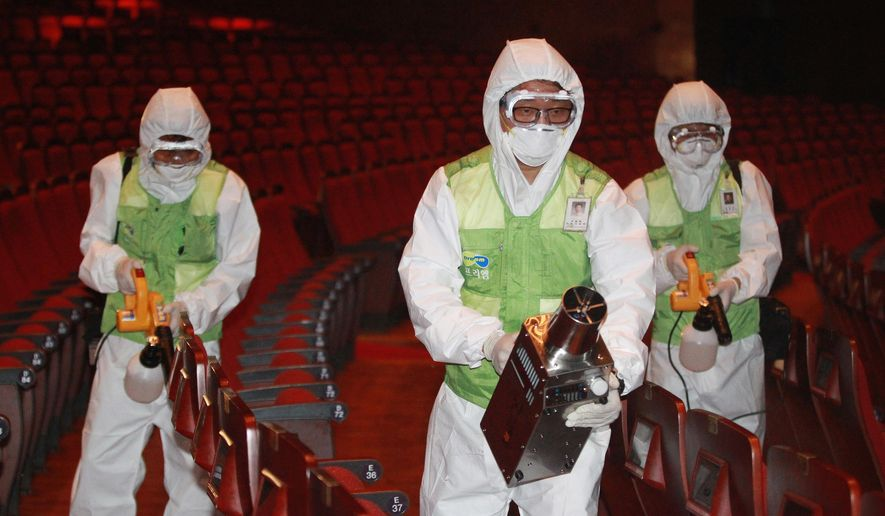 Workers wearing protective gears, spray antiseptic solution as a precaution against the spread of MERS, Middle East Respiratory Syndrome, virus at the Sejong Culture Center in Seoul, South Korea, Tuesday, June 16, 2015. The outbreak of the poorly understood disease has caused widespread fear in South Korea and criticism that health workers and the government failed to initially recognize and quickly contain it. (AP Photo/Ahn Young-joon)