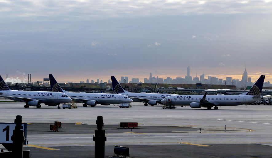 In this May 1, 2015 photo, United Airlines jets are parked at Newark Liberty International Airport as the sun rises behind the New York City skyline, in Newark, N.J. United Airlines on Tuesday, June 16, 2015 said it will stop flying to New York's Kennedy Airport in October and shift the remaining cross-country flights there to its nearby hub in Newark. (AP Photo/Julio Cortez)