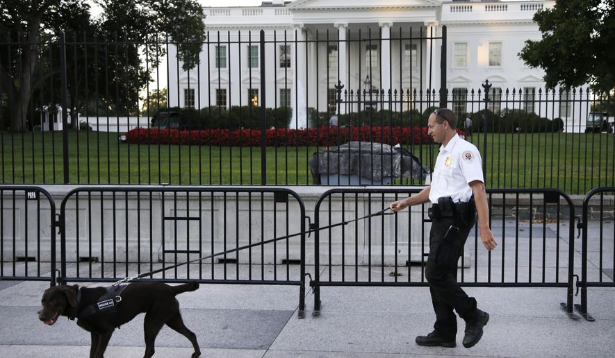 FILE - In this Sept. 22, 2014, file photo, a member of the Secret Service Uniformed Division with a K-9 walks along the perimeter fence along Pennsylvania Avenue outside the White House in Washington. An Army veteran who got over the White House fence and inside the executive mansion before being stopped is about to be sentenced. Omar Gonzalez is scheduled to appear in federal court in Washington for a sentencing hearing Tuesday. Gonzalez's lawyer is asking a judge to sentence him to time served and says he deserves leniency because of his Army service. Prosecutors are asking that Gonzalez spend nearly two years in prison. (AP Photo/Carolyn Kaster, File)
