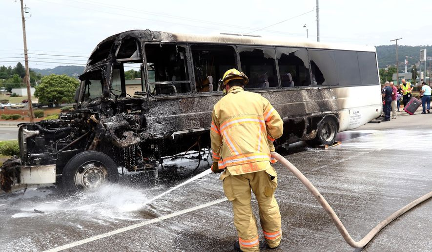 Roseburg Fire Department firefighter Parker Brown responds to a bus that caught fire in Roseburg, Ore., Tuesday, June 16, 2015. The bus was coming from Southern California to Portland, when it caught fire on Interstate 5. (Michael Sullivan/The News-Review via AP)