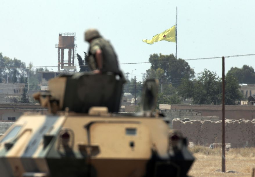 A Turkish soldier on an armored personnel carrier watches as in the background a flag of the Kurdish People's Protection Units, or YPG, is raised over the city of Tal Abyad, Syria, June 16, 2015. (Associated Press) ** FILE **