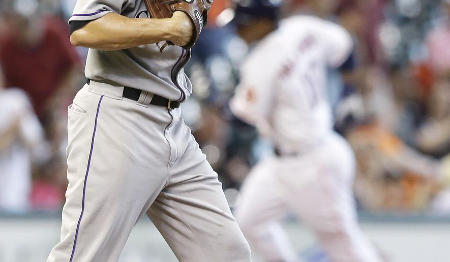 Colorado Rockies starting pitcher Chris Rusin, left, heads back to the mound as Houston Astros' Luis Valbuena rounds the bases after hitting a three-run home run in the third inning of a baseball game Tuesday, June 16, 2015, in Houston. (AP Photo/Pat Sullivan)