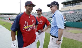 FILE - In this Feb. 25, 2013, file photo, Houston Astros general manager Jeff Luhnow, right, talks to St. Louis Cardinals center fielder Jon Jay, left, and second baseman Daniel Descalso before an exhibition spring training baseball game in Jupiter, Fla.  Major League Baseball says it is cooperating with a federal investigation into an illegal breach of the Astros' internal operations database, amid a report that the Cardinals were responsible for the hack. The New York Times, citing unnamed law enforcement officials, reported Tuesday, June 16, 2015 , that the FBI and Justice Department are investigating whether Cardinals' front-office officials are responsible for the effort to steal information about player personnel. The The teams were rivals in the National League Central until Houston moved to the American League in 2012. (AP Photo/Julio Cortez, File)