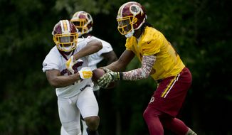 Washington Redskins quarterback Robert Griffin III, right, and running back Chris Thompson, left, take part in drills during NFL football minicamp at Redskins Park Tuesday, June 16, 2015 in Ashburn, Va. (AP Photo/Pablo Martinez Monsivais)