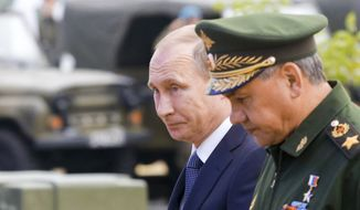 Russian President Vladimir Putin, left, and Defense Minister Sergei Shoigu, right, arrive to attend the opening of the Army-2015 international military show featuring the latest Russian weapons in Kubinka, outside Moscow, Russia, Tuesday, June 16, 2015. Putin said Tuesday the Russian military will receive 40 new intercontinental ballistic missiles this year capable of piercing any missile defenses, a blunt reminder of the nation's nuclear might amid tensions with the West over Ukraine. (Maxim Shemetov/Pool photo via AP)
