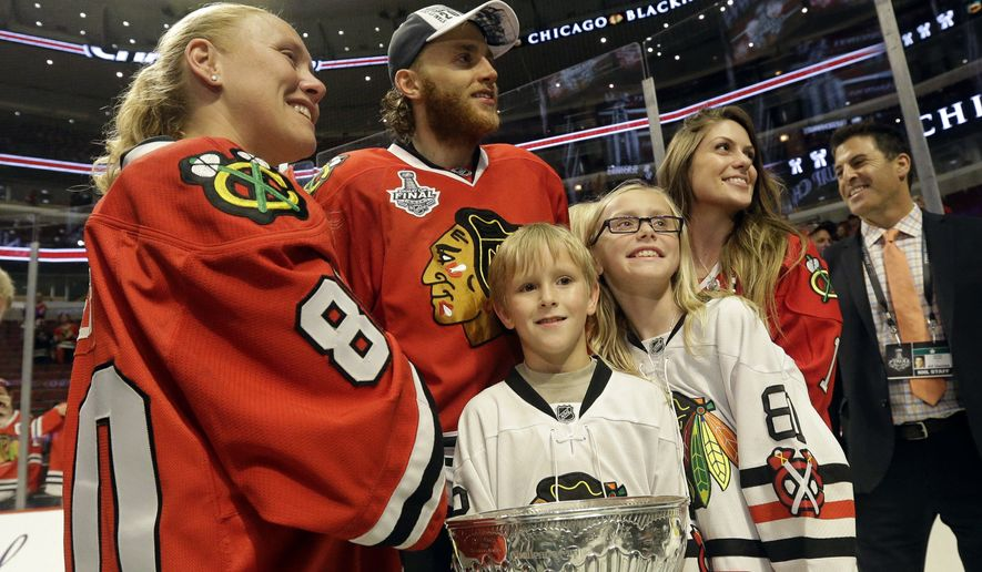 Chicago Blackhawks right wing Patrick Kane (88) celebrates with Kelly Reif, left, widow of former Blackhawks equipment man Clint Reif, who died at his home in December, and her children, after defeating the Tampa Bay Lightning in Game 6 of the NHL hockey Stanley Cup Final series on Monday, June 15, 2015, in Chicago. The Blackhawks defeated the Lightning 2-0 to win the series 4-2. (AP Photo/Nam Y. Huh)