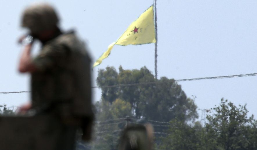 In this photo taken from the Turkish side of the border between Turkey and Syria, in Akcakale, southeastern Turkey, a Turkish soldier stands on an armoured personnel carrier as in the background a flag of the Kurdish People's Protection Units, or YPG, is raised over the town of Tal Abyad, Syria, Tuesday, June 16, 2015. Kurdish fighters with the YPG along with their allies Free Syrian Army, took full control of Tal Abyad on Tuesday, dealing a major blow to the Islamic State group's ability to wage war in Syria. Mopping up operations have started to make the town safe for the return of residents, after more than a year of State group militants holding control of the town.(AP Photo/Lefteris Pitarakis)