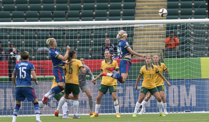 Sweden's Amanda Ilestedt (14) heads the ball as Australia defends during the first half of a FIFA World Cup soccer match in Edmonton, Alberta, Canada, on Tuesday, June 16, 2015. (Jason Franson/The Canadian Press via AP)