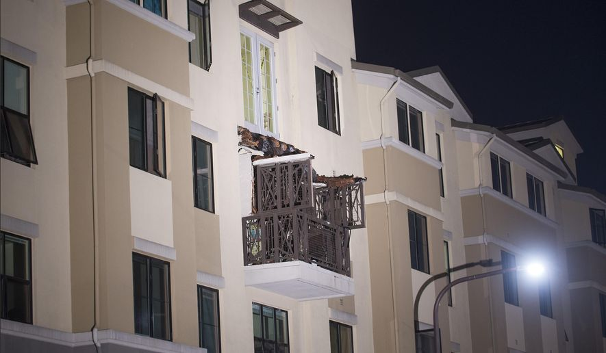 A fourth floor balcony rests on the balcony below after collapsing at the Library Gardens apartment complex in Berkeley, Calif., early Tuesday, June 16, 2015. Berkeley police say several people are dead and others injured after the balcony fell shortly before 1 a.m., near the University of California, Berkeley. (AP Photo/Noah Berger)