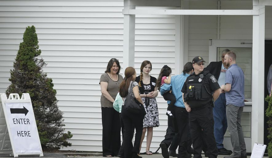 Mourners walk past a Hudson, Mass., law enforcement official, front right, as they enter Grace Baptist Church, Tuesday, June 16, 2015, in Hudson, during a wake for KeithBroomfield who was killed in Syria while fighting the Islamic State group. Broomfield, 36, of Westminster, is believed to be the first U.S. citizen to die fighting alongside Kurdish forces against Islamic State. (AP Photo/Steven Senne)
