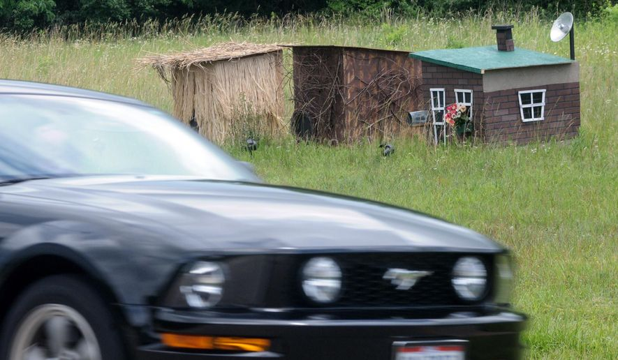 Three houses, one made of hay, one of sticks and one of bricks, have been constructed along U.S. Route 35 in Xenia Township west of Dayton, Ohio, Monday, June 15, 2015. An anonymous apparent fan of pigs and fairy tales is offering some shelter for any piglets still loose after a semitrailer crash last week in southwest Ohio. (Marshall Gorby/The Dayton Daily News via AP)