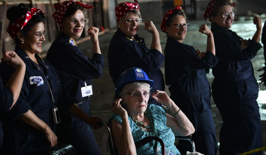 Vivian Litchard, 91, poses with volunteer Tribute Rosie the Riveters inside the future home of the National Museum of Aviation and Technology at Willow Run Airport in Ypsilanti, Mich., on Tuesday, June 16, 2015. Litchard was one of the first female workers in the Willow Run factory. (Alex McDougall/The Ann Arbor News via AP) LOCAL TELEVISION OUT; LOCAL INTERNET OUT