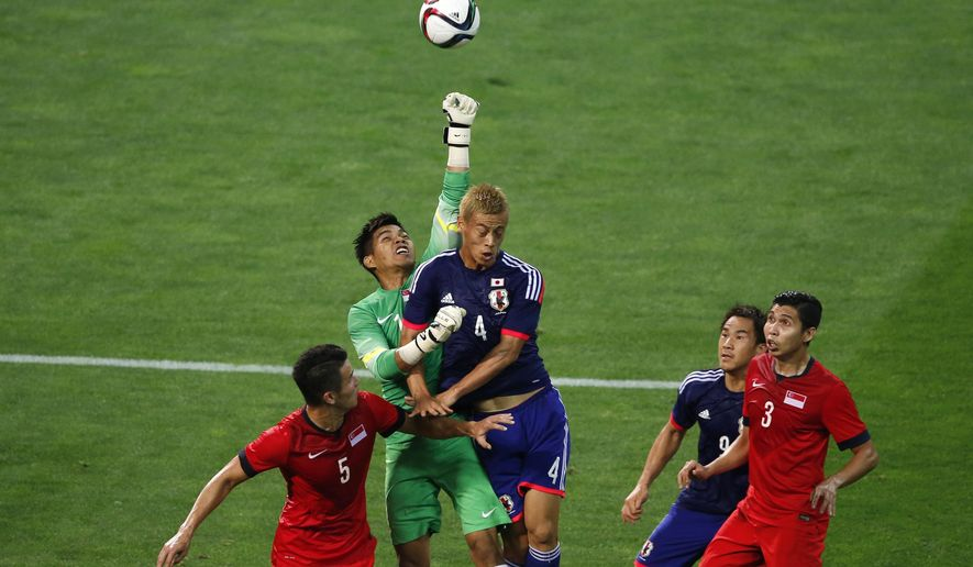 Japan's Keisuke Honda, center right, and Singapore's goalkeeper Mohamad Izwan Bin Mahbud, center left, vie for the ball during their second round soccer match of regional qualifiers for the 2018 World Cup, in Saitama, north of Tokyo, Tuesday, June 16, 2015. (AP Photo/Shuji Kajiyama)