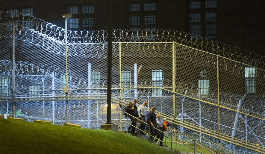 Corrections officers walk next to a fence covered in razor wire as they leave work at the Clinton Correctional Facility, Monday, June 15, 2015 in Dannemora, N.Y. State police say more than 800 law enforcement officers are pushing on in the hunt for convicted murderers David Sweat and Richard Matt 10 days after the two escaped from the maximum-security prison in rural New York. (AP Photo/Mark Lennihan)